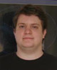 Man in dark t-shirt with dark background.