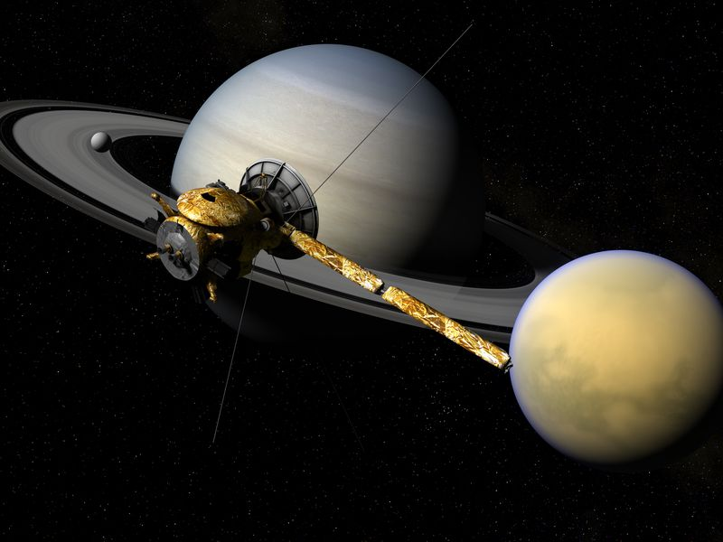 Large banded sphere with rings, a smaller reddish sphere and spacecraft with dish antenna and long solar panel, on black background.