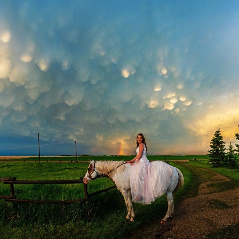 Young woman in long white dress on white horse under sky with many small, sunlit downward bulges from a dark cloud.