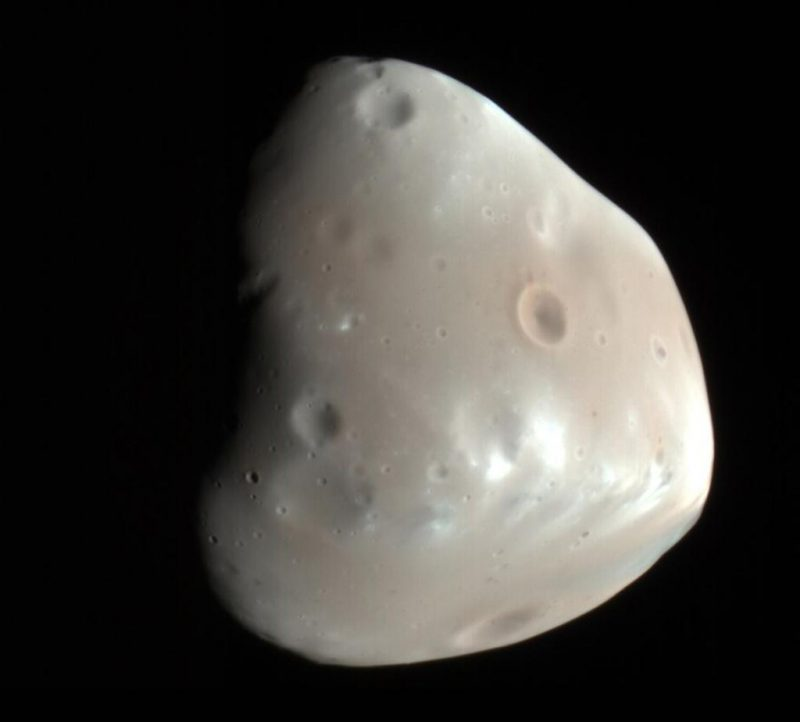 Mostly smooth, grayish, irregular rocky object with a few small craters, against black background.