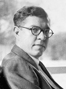 An intelligent-looking man in glasses and a suit.