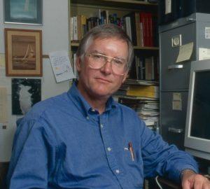 Man in blue shirt sitting at desk.