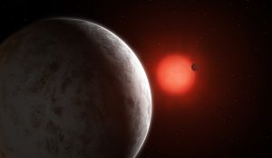 Two planets orbiting a red star with other stars in background.