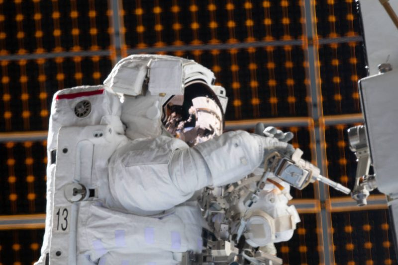Astronaut in a white spacesuit, intently working on machinery, against dark flat surface with small orange dots.