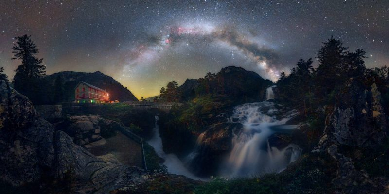 Milky Way arching over streaming waterfall in hills with nearby evergreen trees.