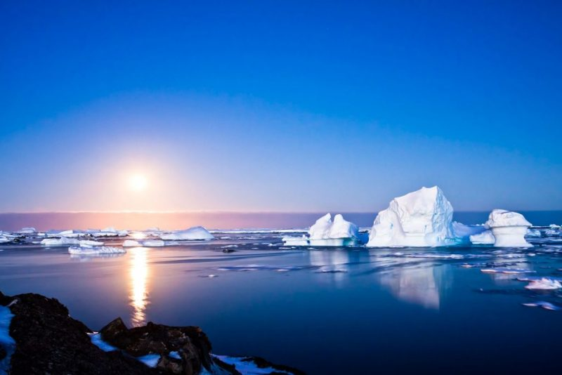 Low, bright sun over blue sea with wmall icebergs and floating ice under blue sky.