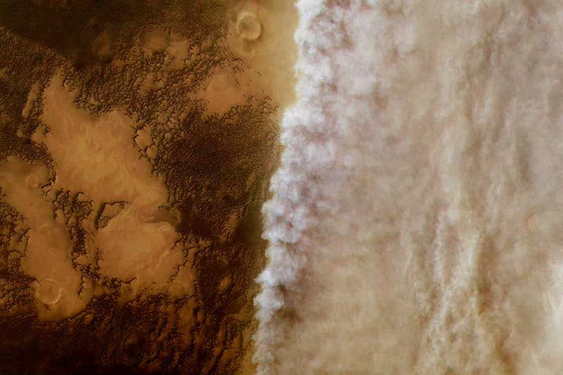 Orbital view of brownish terrain on left and billowing cloud-like patterns on right.
