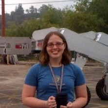 Smiling woman in blue shirt with wheeled apparatus behind her.