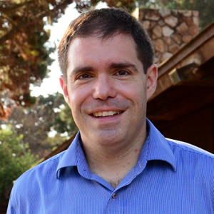 Smiling man in blue shirt with trees in background.