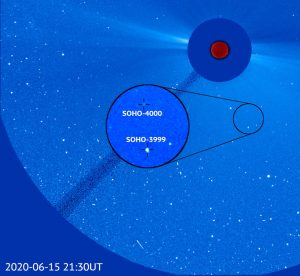 A rounded field of view, with the sun obscured behind a disk to mask its brightness, and 2 small comets (with short visible tails) moving near the sun.
