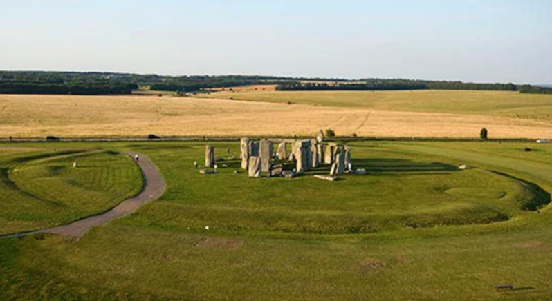 Group of vertical stones in the middle of a large ditch.