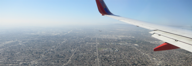 View over the wing of an airplane of hazy skies and a city spread out below.