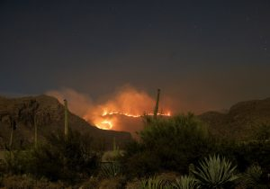 A fire, at night, in distant mountains, with a desert landscape in the foreground.