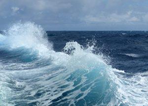 Breaking blue wave with white foam.