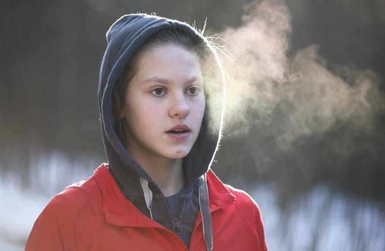Young girl in hooded jacket with clouds of vapor in front of her face.