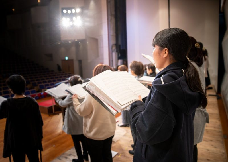 People on a stage singing with open books.