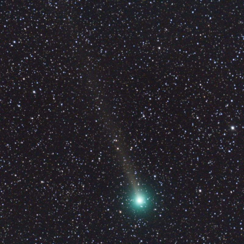 A large green fuzzy spot with long tail against a dense star field.