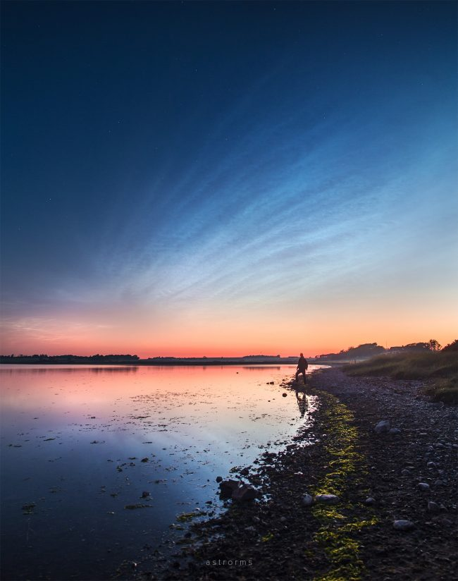 High, rippled, shining clouds above waterway in twilight, man standing on beach.