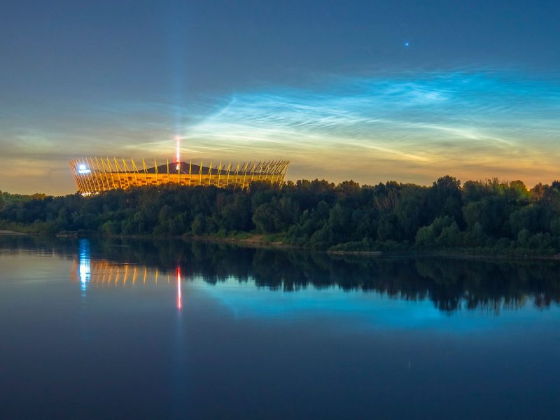 Electric blue noctilucent clouds shining above a river with a lit-up stadium in the distance.