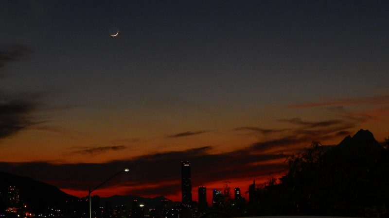 Very thin young moon beautifies deep blue and maroon evening twilight above a city skyline.