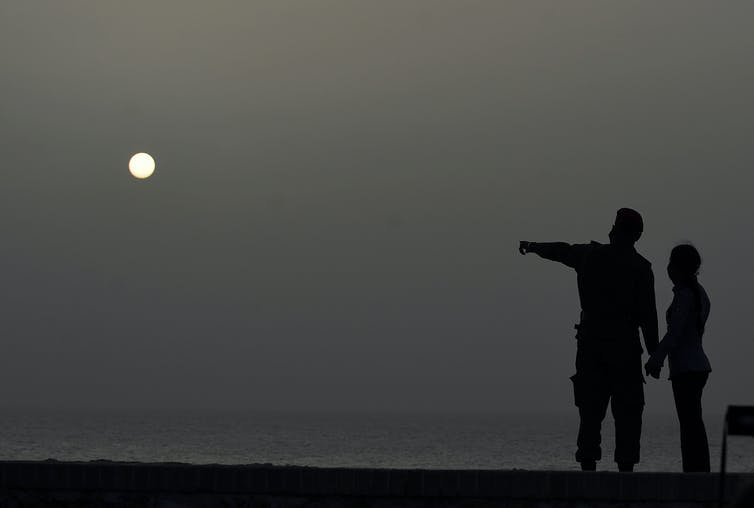 Silhouettes of two people against dark gray sky with dim sun.