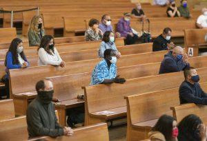 People in masks sitting spaced apart in pews.