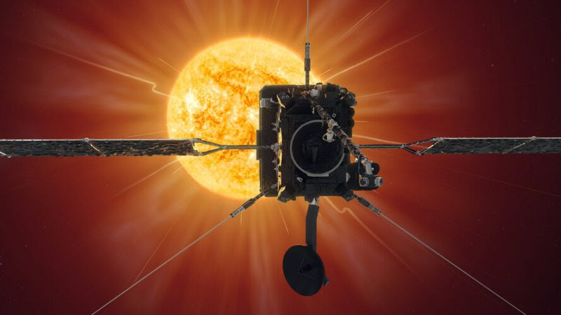A square spacecraft, with solar panel wings and what looks like a large camera 'eye,' with the sun in the background.