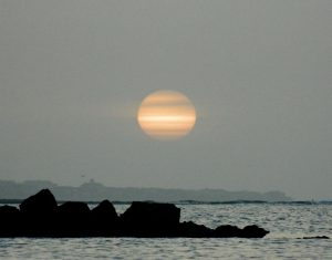 A very dusty sunrise - with layers of dust over the sun - above a rocky coastline and ocean.