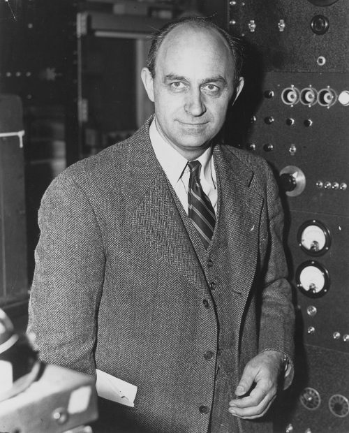 An intelligent-looking man in a suit with a big control panel behind him.