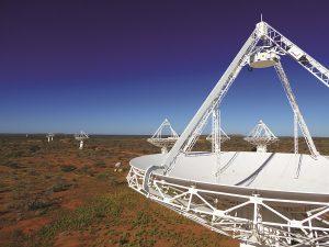 Radio telescopes on desert terrain with blue sky.