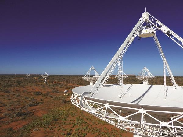 Array of dish-shaped radio telescopes on desert terrain with blue sky.
