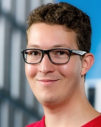 Smiling young man with eyeglasses and buildings in background.