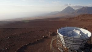 Telescope on a desert plain, with mountains in the background.