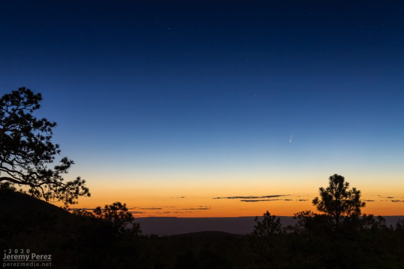 A small faint comet in a twilight sky, with a desert landscape silhouetted in the foreground.