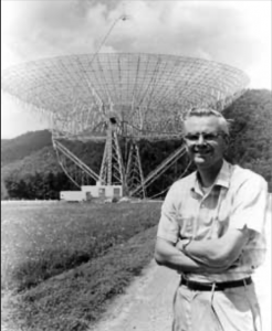 Young scientist, arms folded, standing in front of dish-type radio telescope.
