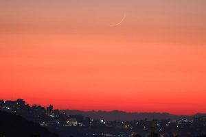 Very thin yellow crescent moon in orange twilight sky over village lights.