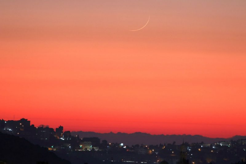Very thin yellow crescent moon high in orange twilight sky over village lights.