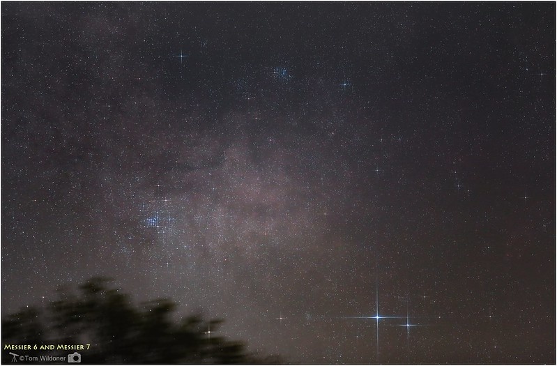 A photo showing two close-together, brilliant stars with two patches of multiple stars nearby.