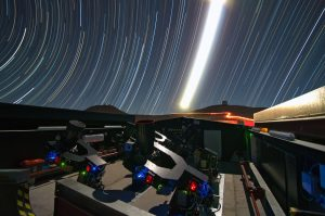 Telescopes on ground with bright curved light trails in the sky.
