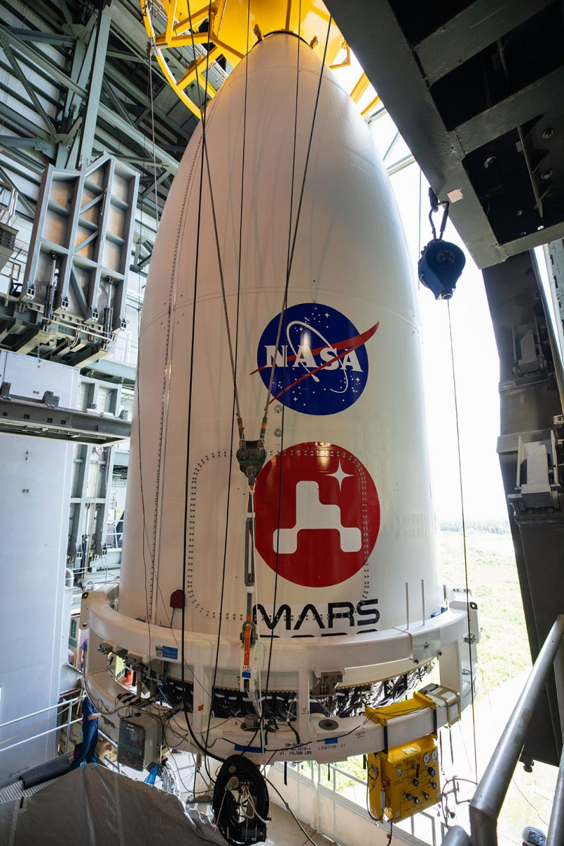 Tall, rounded, white cone with NASA and Perseverance logos on it.
