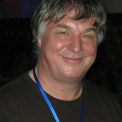 Smiling man with blue ribbon around his neck on black background.