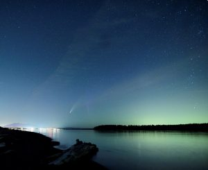 Comet and aurora, over a body of water.