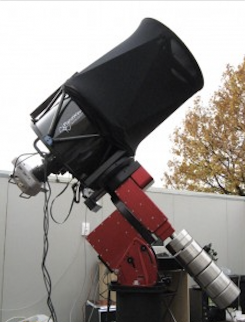 Short, thick black telescope outside in front of a telescope shelter.