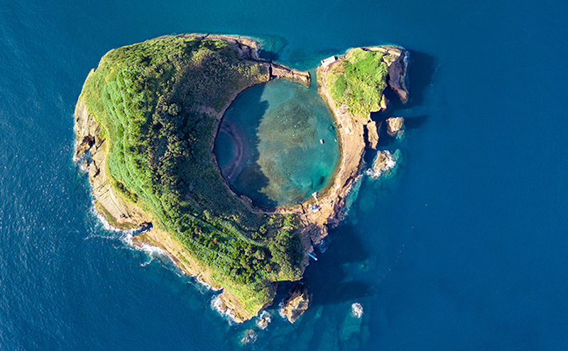 Aerial view of a rocky, wooded island with a circular water-filled crater in the middle.
