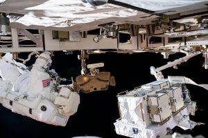 Two astronauts in spacesuits outside spacecraft.