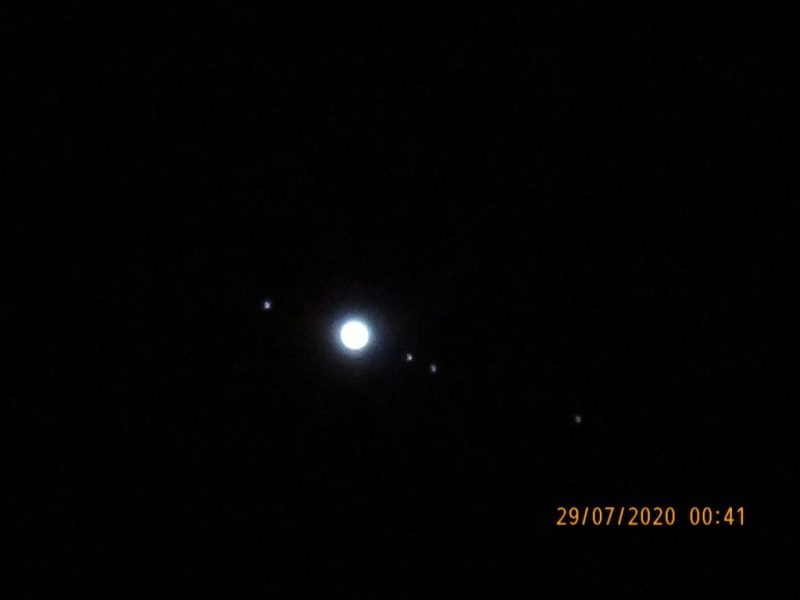 A disk, Jupiter, with 4 dots, the moons, in a line bisecting it.