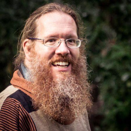 Smiling man with medium-long gray-streaked beard.