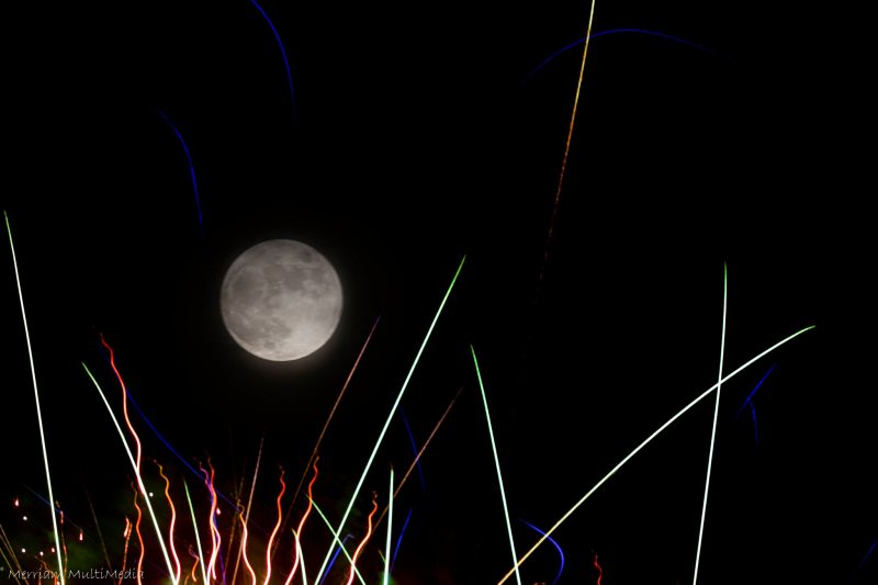 A cropped photo with the full moon above some sparks from fireworks.