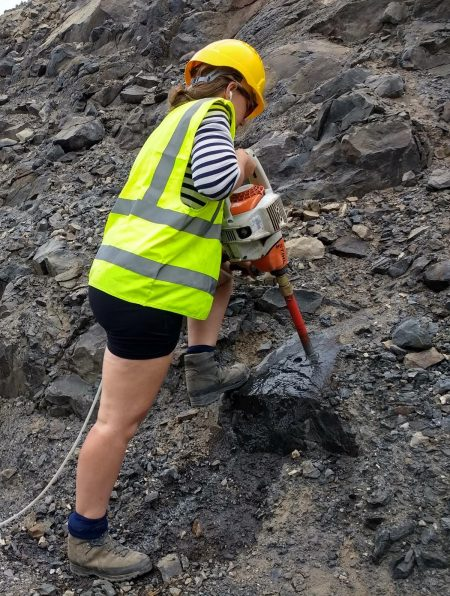 Female scientist with neon green vest and yellow hard hat operating a large drill.