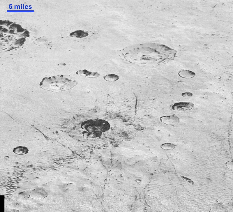 A few large scattered craters on a white surface.